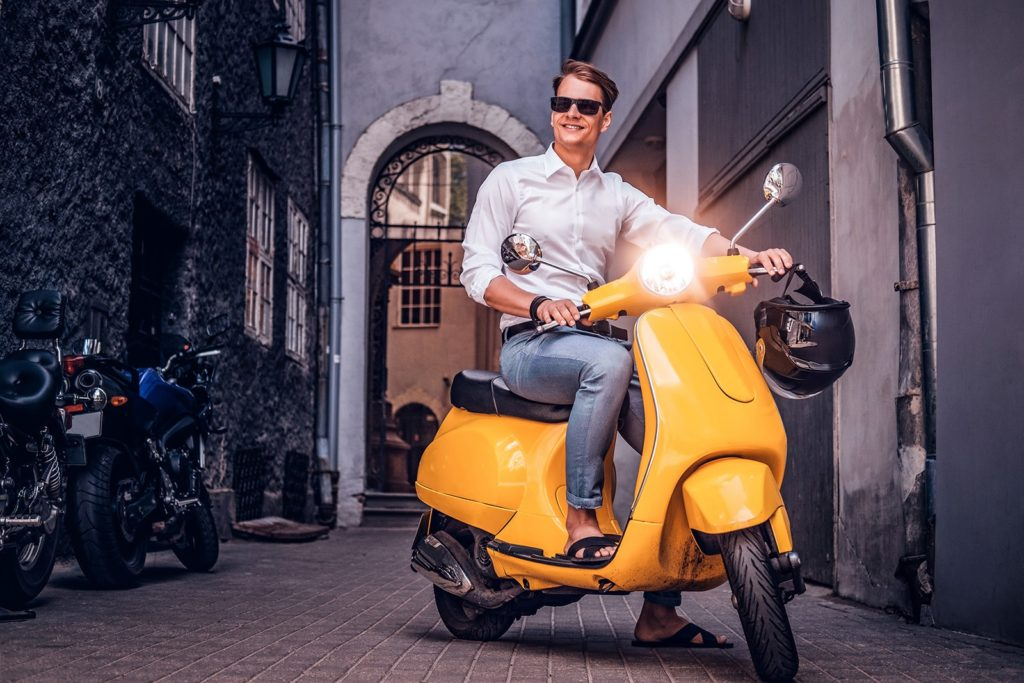 handsome-man-riding-on-vintage-italian-scooter-in